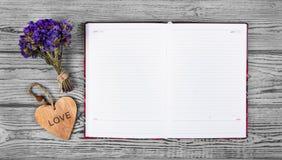 Öppna anteckningsboken med tomma sidor och trähjärta på en grå bakgrund kopiera avstånd royaltyfria bilder