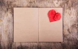 Öppna anteckningsboken med tomma sidor och valentinorigami Röd origamihjärta på en ren sida Begreppet av dagen för valentin` s Arkivbilder