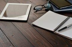 Öppna anteckningsboken, minnestavladatoren, exponeringsglas och läderaffärsfolen Arkivfoton
