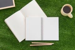 Öppna anteckningsboken och blyertspennan på gräsfält Arkivbilder