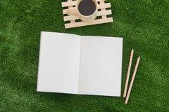 Öppna anteckningsboken och blyertspennan på gräsfält Royaltyfria Foton