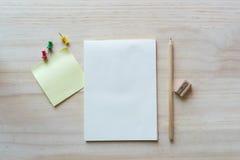 Öppna anteckningsboken och den klibbiga anmärkningen på träbakgrund Royaltyfria Foton
