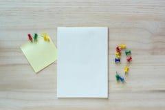 Öppna anteckningsboken och den klibbiga anmärkningen på träbakgrund Arkivbild