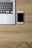 Öppna anteckningsboken och smartphonen på träbakgrund Royaltyfria Foton