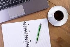 Öppna anteckningsboken på skrivbordet Arkivbild