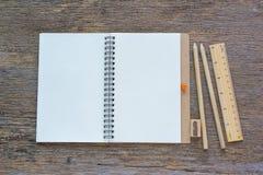 Öppna anteckningsboken på träbakgrund med blyertspennor och linjalen Arkivfoton