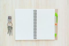 Öppna anteckningsboken på träbakgrund med pennan Arkivfoto