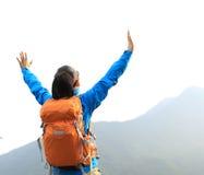 Öppna armar för kvinnafotvandrare på klippan för bergmaximum Arkivfoto