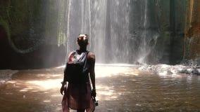 Öppna armar för ung kvinna till den fantastiska vattenfallet i Bali