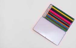 Öppna asken med blyertspennor på arket av papper royaltyfri bild
