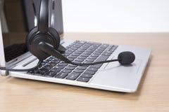 Öppna bärbar datordatoren med hörlurar med mikrofon royaltyfri foto