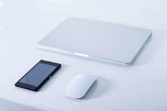 Öppna bärbara datorn med den svarta smartphonen Royaltyfri Bild