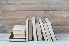 Öppna böcker på trätabellen, svart brädebakgrund tillbaka skola till Utbildningsaffärsidé Arkivbilder
