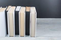 Öppna böcker på trätabellen, svart brädebakgrund tillbaka skola till Utbildningsaffärsidé Arkivfoton