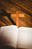 Öppna bibeln med korssymbolen bakom Arkivfoton