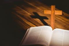 Öppna bibeln med korssymbolen bakom Royaltyfria Bilder