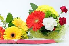 Öppna bibeln och härliga blommor på vit bakgrund Royaltyfri Bild