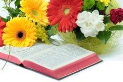 Öppna bibeln och härliga blommor på vit bakgrund Arkivfoton