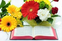 Öppna bibeln och härliga blommor på vit bakgrund Arkivfoto
