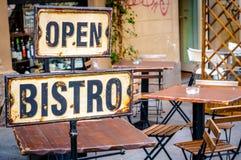 Öppna bistroer undertecknar på den tomma caffeterrassen Arkivfoto