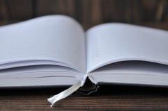 ?ppna bok- eller anteckningsbokl?gner p? en tr?tabell royaltyfri foto