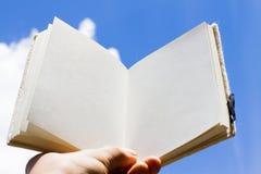 Öppna bok- och himmelbakgrund Arkivfoton