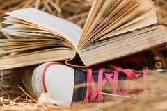 Öppna bok- och sportskor Royaltyfria Bilder