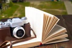 Öppna bok- och tappningkameran på tabellen kopiera avstånd Royaltyfri Fotografi