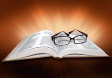 Öppna bokbibeln med korset och exponeringsglas Arkivfoton