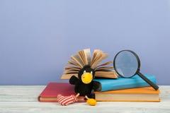 Öppna boken, färgrika böcker för inbunden bok på trätabellen Förstoringsapparat leksakgalande tillbaka skola till Kopiera utrymme Arkivbilder