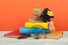 Öppna boken, färgrika böcker för inbunden bok på trätabellen Förstoringsapparat leksakgalande tillbaka skola till Kopiera utrymme Arkivfoton