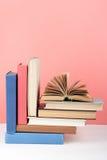Öppna boken, färgrika böcker för inbunden bok på trätabellen, röd rosa bakgrund tillbaka skola till Kopiera utrymme för text Utbi Royaltyfria Bilder