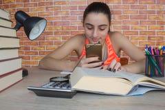 Öppna boken, färgrika böcker för inbunden bok på trätabellen Ung flickasammanträde på det hemmastadda skrivbordet och att göra lä Royaltyfria Foton