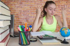 Öppna boken, färgrika böcker för inbunden bok på trätabellen Ung flickasammanträde på det hemmastadda skrivbordet och att göra lä Royaltyfria Bilder