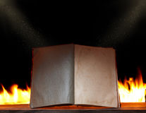 Öppna boken i omgivande lampa med brand Royaltyfri Foto