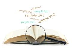 Öppna boken med förstoringsglaset över vit bakgrund Arkivbild