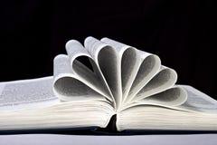 Öppna boken med sidorna som krullas på en svart Fotografering för Bildbyråer