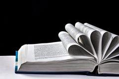 Öppna boken med sidorna som krullas på en svart Arkivbild