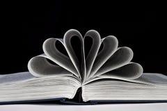 Öppna boken med sidorna som krullas på en svart Arkivfoto