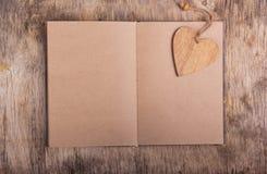 Öppna boken med tomma sidor och en bokmärke som göras av trä Det pappers- hålet rev sönder i hjärta Shape med gammal Wood bakgrun Royaltyfria Foton