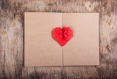 Öppna boken med tomma sidor och origami för en pappershjärta Valentinorigami valentin för dag s kopiera avstånd Royaltyfria Bilder