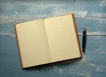 Öppna boken med tomma sidor på trätabellen royaltyfria bilder