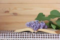 Öppna boken och en filial av den blommande lilan på tabellen Kopia Spac fotografering för bildbyråer