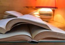 Öppna boken och en tabelllampa Fotografering för Bildbyråer