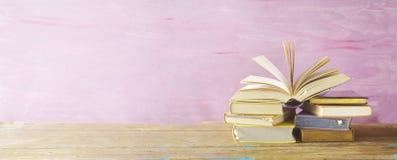 Öppna boken på en bunt av böcker, arkivbild