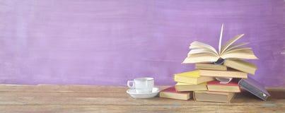 Öppna boken på en hög av gamla böcker och en kopp kaffe Arkivbild