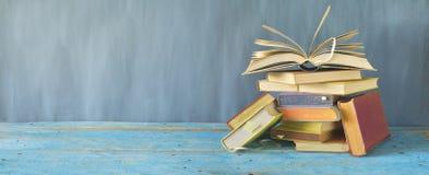 Öppna boken på en hög av gamla böcker, panorama arkivfoton