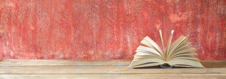 Öppna boken på röd grungy bakgrund Arkivfoto