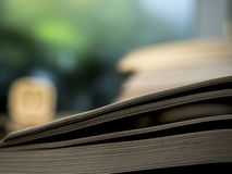 Öppna boken på tabellen med suddig bakgrund Arkivbild