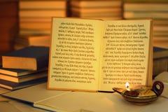 Öppna boken som är upplyst vid en olje- lampa Iliadöppningslinjer Arkivbild
